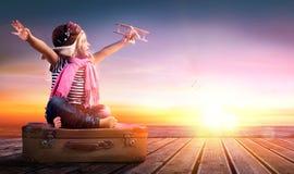 Traumreise - kleines Mädchen auf Weinlese-Koffer Lizenzfreie Stockbilder