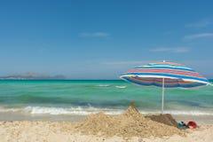 Traumstrand in der Bucht von Alcudia in Majorca mit Regenschirm und Sandburg stockfotografie