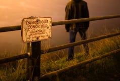 Traurig/drückte den Mann nieder, der auf eine Klippe hinter einem Warnschild steht lizenzfreie stockfotos