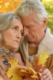Traurige ältere Paare, die draußen umfassend stehen Stockbild