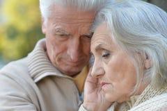 Traurige ältere Paare, die draußen umfassend stehen Stockbilder