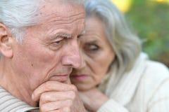 Traurige ältere Paare, die draußen umfassend stehen Stockfotos