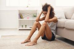 Traurige Afroamerikanerfrau auf Boden zu Hause Stockbilder