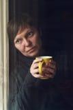 Traurige alleinfrauen-trinkender Kaffee in der Dunkelkammer Lizenzfreie Stockfotografie