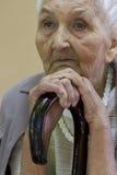 Traurige alte Dame, die mit Spazierstock erwägt Lizenzfreie Stockbilder