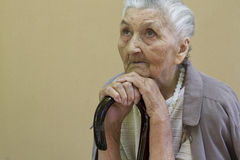 Traurige alte Dame, die mit Spazierstock erwägt Stockfoto