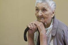 Traurige alte Dame, die mit Spazierstock erwägt Stockfotografie