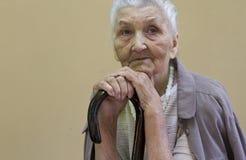 Traurige alte Dame, die mit Spazierstock erwägt Stockfotos