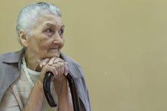 Traurige alte Dame, die mit Spazierstock erwägt Lizenzfreies Stockfoto