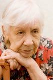 Traurige alte Frau in einem Raum Lizenzfreies Stockfoto