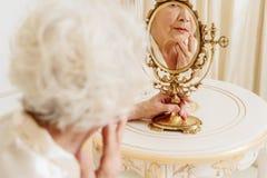 Traurige alte Frau, ihre Gesichtsreflexion beobachtend stockfotos