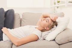 Traurige blonde Mädchengefühlsschmerz, die auf Sofa liegen Lizenzfreies Stockfoto