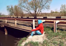 Traurige brütende Frau der Seitenansicht, die an der Brücke nahe bei dem Fluss sitzt Ein junges Mädchen schaut unten traurig stockfoto