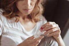 Traurige Dame, die zu Hause Pillen einnimmt Stockfotografie
