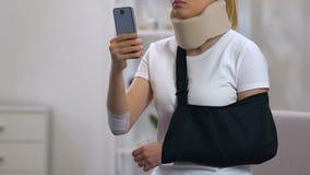 Traurige Dame im zervikalen Kragen- und Armriemen schreibend auf Smartphone, Autounfall stock footage