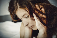 Traurige deprimierte Frau auf Bett Lizenzfreie Stockfotos