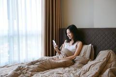 Traurige deprimierte Frau, die auf Bett im Luxusschlafzimmer denkt Stockfotos
