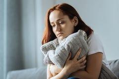 Traurige deprimierte Frau, die ein Kissen umarmt Stockbild
