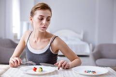 Traurige deprimierte Frau, welche die Pillen betrachtet Lizenzfreie Stockfotografie