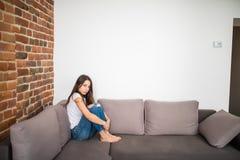 Traurige deprimierte Frau, zu Hause, das sie auf der Couch sitzt Einsamkeits- und Traurigkeitskonzept Stockbilder