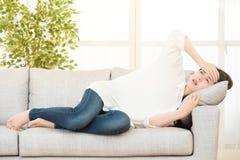 Traurige deprimierte Frau zu Hause, die auf der Couch sitzt Stockbilder
