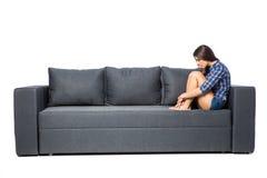 Traurige deprimierte Frau zu Hause, sitzt sie auf dem Couch-, Einsamkeits- und Traurigkeitskonzept Lizenzfreies Stockbild