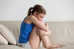 Traurige deprimierte junge Frau, die auf dem Sofa umfasst ihre Knie sitzt Stockfoto