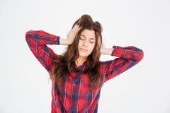 Traurige deprimierte junge Frau mit den Händen auf Haupt, Kopfschmerzen habend Lizenzfreie Stockfotos