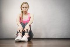 Traurige deprimierte junge Jugendliche, die durch Wand sitzt Stockbild