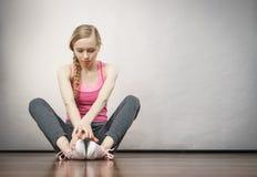 Traurige deprimierte junge Jugendliche, die durch Wand sitzt Stockfotografie