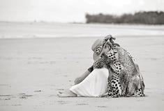Traurige deprimierte Sorgen machende Frau, die allein auf leerem Strand sitzt Lizenzfreies Stockbild