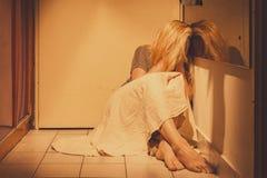 Traurige, deprimierte und einsame Frau, die auf Bodenfliesen, in einem Rock, barfuß sitzt Lizenzfreie Stockbilder
