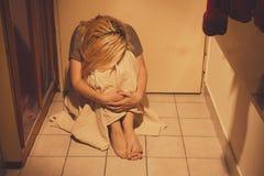 Traurige, deprimierte und einsame Frau, die auf Bodenfliesen, in einem Rock, barfuß sitzt Lizenzfreies Stockbild
