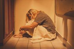Traurige, deprimierte und einsame Frau, die auf Bodenfliesen, in einem Rock, barfuß sitzt Lizenzfreies Stockfoto
