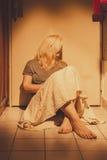 Traurige, deprimierte und einsame Frau, die auf Bodenfliesen, in einem Rock, barfuß sitzt Stockfotos