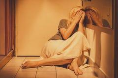 Traurige, deprimierte und einsame Frau, die auf Bodenfliesen, in einem Rock, barfuß sitzt Stockbild
