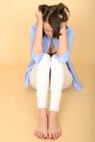 Traurige deprimierte und verärgerte junge Frau, die auf dem Boden sitzt Stockbild