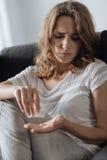 Traurige deprimierte unglückliche Frau, die Beruhigungsmittel nimmt Stockfotografie