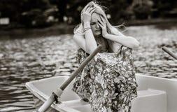 Traurige drepressed Frau, die allein auf einem Reihenboot sitzt lizenzfreie stockbilder