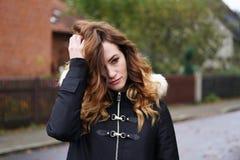 Traurige einsame deprimierte junge Frau, die ihr Haar kräuselt Lizenzfreie Stockbilder