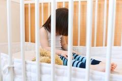 Traurige einsame 2 Jahre Kleinkind, die im weißen Bett sitzen Stockfoto