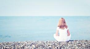 Traurige einsame junge Schönheit, die zurück auf Strand das Meer sitzt Lizenzfreie Stockbilder