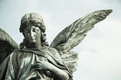 Traurige Engelsskulptur mit offenen langen Flügeln über dem Rahmen desaturated gegen einen hellen weißen Himmel Die traurige Skul stockfoto