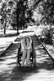 Traurige erwachsene Frau auf Rollstuhl im Park Stockfotografie