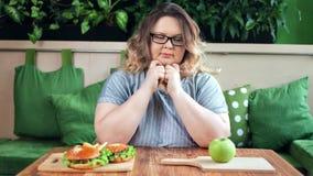 Traurige fette Frau auf der Diät, die Wahl mittlerer Nahaufnahme zwischen Schnellimbiß und des frischen grünen Apfels trifft stock video