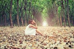 Traurige Frau übergibt weg von ihrem Gesicht so traurig sitzend auf trockenem Blatt in Stockbild
