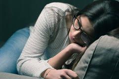 Traurige Frau auf der Couch zu Hause Lizenzfreie Stockfotografie