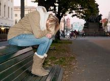 Traurige Frau auf einer Bank Stockfoto