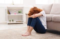 Traurige Frau, die allein auf dem Boden sitzt Stockbilder