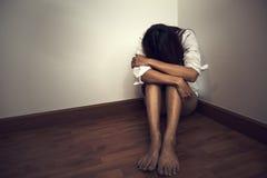 Traurige Frau, die allein in einem leeren Raum sitzt Stockfotos